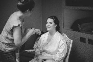 Bride sitting in chair getting makeup done